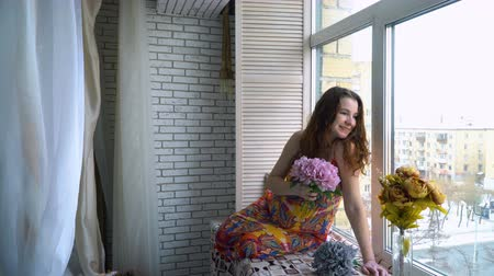 Young beautiful pregnant girl sits near a window
