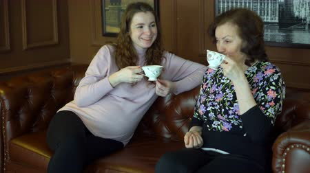 Mother and pregnant daughter in a bright room are sitting on the couch, drinking hot tea and talking about the secrets of women