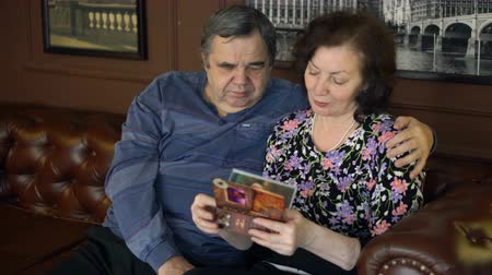 An elderly couple looks at photos in a family photo album.