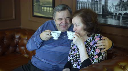 An elderly couple drinks hot tea and laughs.