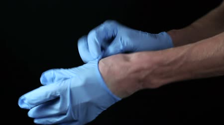 tű : The doctor puts on disposable gloves. Hands on a black background Stock mozgókép