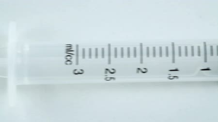injetar : A syringe lying on a white table