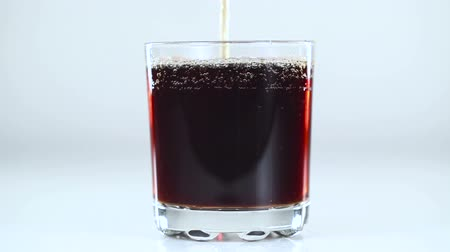 kola : Fizzy drink is poured into a glass. White background. Close-up