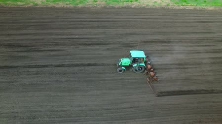field survey : Tractor in a field brings fertilizer into the soil. Early spring. aerial survey 4k Stock Footage