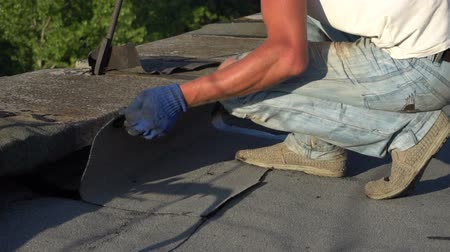 zastřešení : Worker repairing the roof of the house. Lays roofing material. Slow motion
