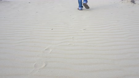 step : Man walking on the sands of the desert. In the picture, only the legs. Slow motion