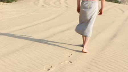 ślady stóp : A man walks on the sand in the desert, the last effort. Visible only to the legs