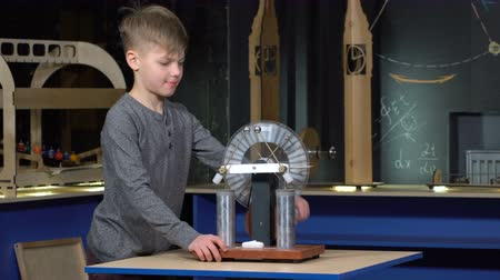 electrostatic : The boy turns the electrostatic machine at a physics lesson