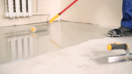 installation lectrique : The builder smooths the studded roller with a liquid floor with a solution of gypsum