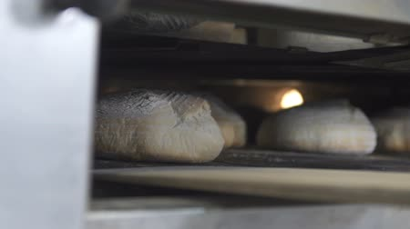 ベイカー : Take out the finished bread from the oven. slow motion 動画素材