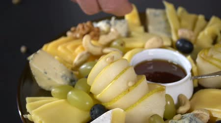 picado : Cheese platter sprinkled with pine nuts. slow motion Stock Footage