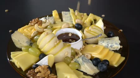 produtos lácteos : Cheese platter sprinkled with pine nuts. slow motion Vídeos