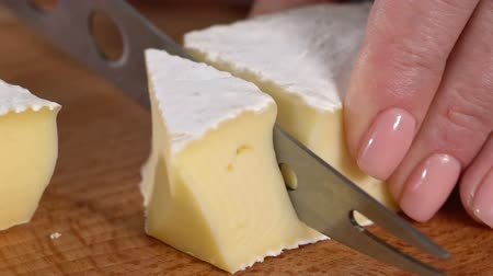 foco no primeiro plano : Cheese with mold cut with a knife. slow motion