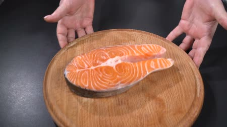 kroutit : Salmon steak on a cutting board. Slow motion