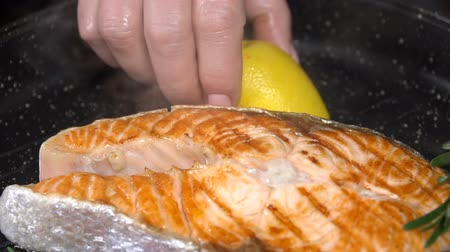 pan fried : Salmon steak with lemon in a pan. Slow motion