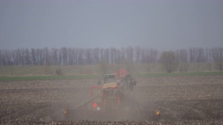 seeder : Tractor sows a field in spring