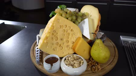 пармезан : Types of cheeses with nuts and fruit on the table Стоковые видеозаписи