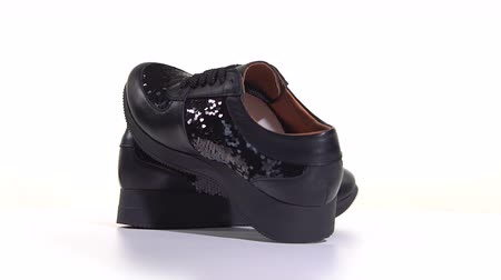 döner : Womens black sneakers on a white background Stok Video