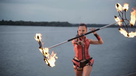 feiticeiro : Girl with a torch fire show on the river bank at sunset. slow motion