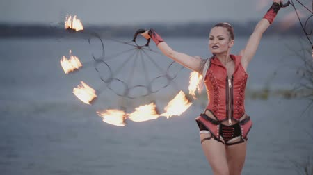 bodywarmer : Girl with a torch fire show on the river bank at sunset. slow motion