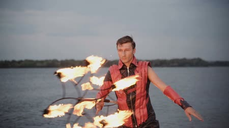 malabarista : Man with torch fire show on the river bank at sunset. slow motion Archivo de Video
