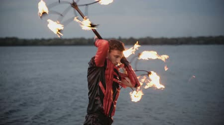 balanceamento : Man with torch fire show on the river bank at sunset. slow motion Stock Footage