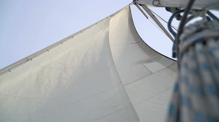 yat yarışı : Mast with a white sail on a yacht in the Black Sea. slow motion