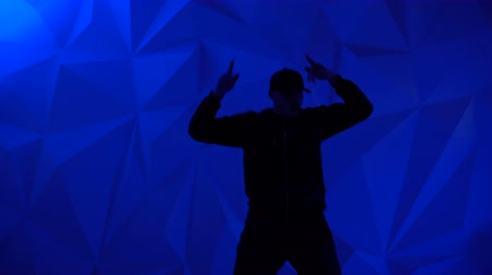 rapper : Rapper man dancing to the music. Silhouette on a dark red background