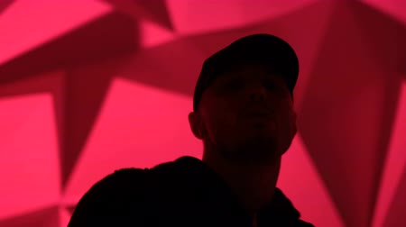 músico : Rapper man dancing to the music. Silhouette on a dark red background