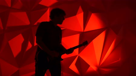 strum : The musician plays the guitar. Guitarist silhouette on red background. Background photography in a photo studio