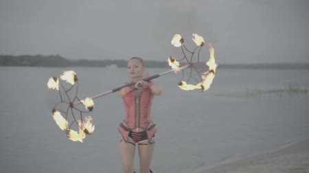 bodywarmer : Girl with a torch fire show on the river bank at sunset. slow motion S-Log3, S-Gamut3, Cine
