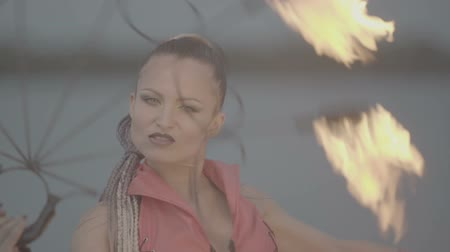 feiticeiro : Girl with a torch fire show on the river bank at sunset. slow motion S-Log3, S-Gamut3, Cine