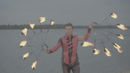 balanceamento : Man with torch fire show on the river bank at sunset. slow motion S-Log3, S-Gamut3, Cine