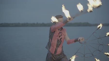 só : Man with torch fire show on the river bank at sunset. slow motion S-Log3, S-Gamut3, Cine