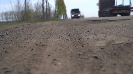 koşullar : Cars drive along an old asphalt road with potholes