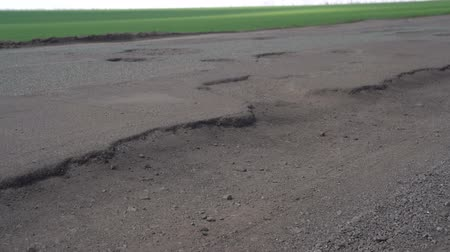 chodnik : Cars drive along an old asphalt road with potholes