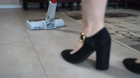 entretien ménager : The girl cleans the flooring in the room with a hand vacuum cleaner Vidéos Libres De Droits