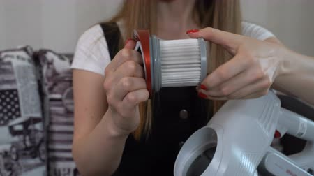 yarık : The girl takes out the filter from the vacuum cleaner on the battery