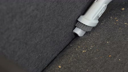 arrumado : Vacuuming a sofa dirty from bread crumbs
