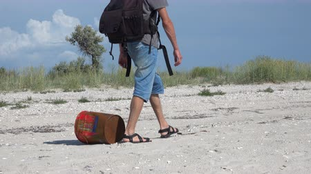 sand bank : A man walks past a rusty iron can on the Black Sea coastline Stock Footage