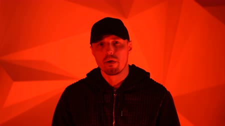 zenekar : Rapper guy rap in front of the camera on a red background Stock mozgókép