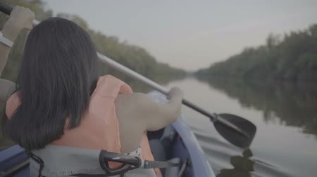 canoe kayak : A girl floats in a kayak boat on the river and rowing an oar. Slow motion