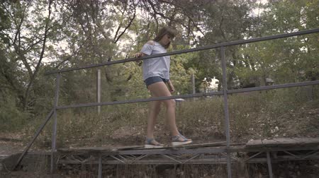 expedição : Girl crosses an old broken wooden bridge in the park
