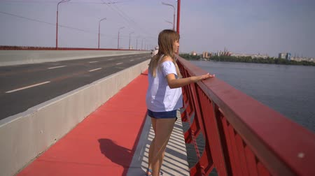 sobre o branco : A young girl walks on a new bridge over the Dnieper River Vídeos