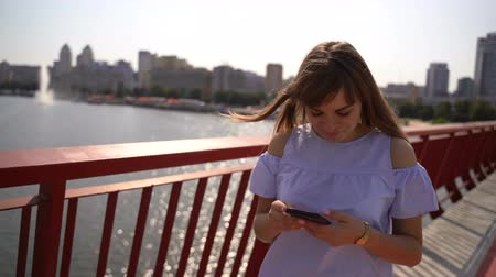 corrimão : A girl walks on a bridge over a river and talks on the phone