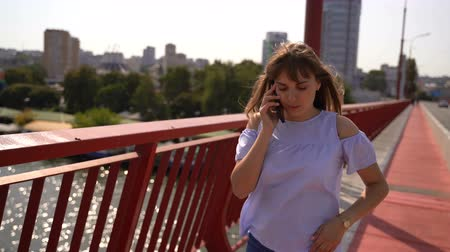 handrails : A girl walks on a bridge over a river and talks on the phone