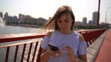 auscultadores : A young girl walks on the bridge and listens to music from the phone Stock Footage