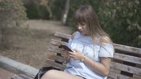 amigo : Girl with a phone sits on a wooden park bench Vídeos
