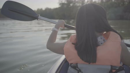каноэ : A girl floats in a kayak boat on the river and rowing an oar Стоковые видеозаписи