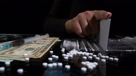 kola : White cocaine powder on a table with dollar bills and a syringe Stok Video